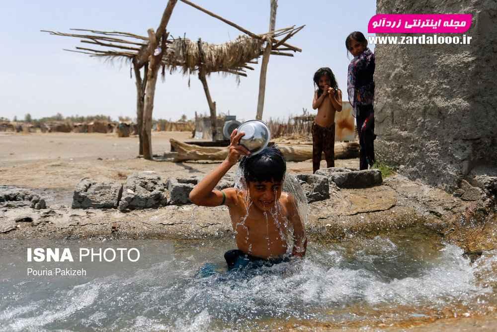 کودکان روستا «مزرعه» در حال آب تنی و استهحمام در دمای بالای ۴۵ درجه با آب موتور هستند.