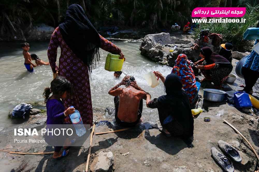 خانوادهای در حال استحمام پدربزرگشان در برکهای که در مجاورت روستا ایجاد شده و از همان آب برای شستن ظروف ولباسها استفاده میکنند.