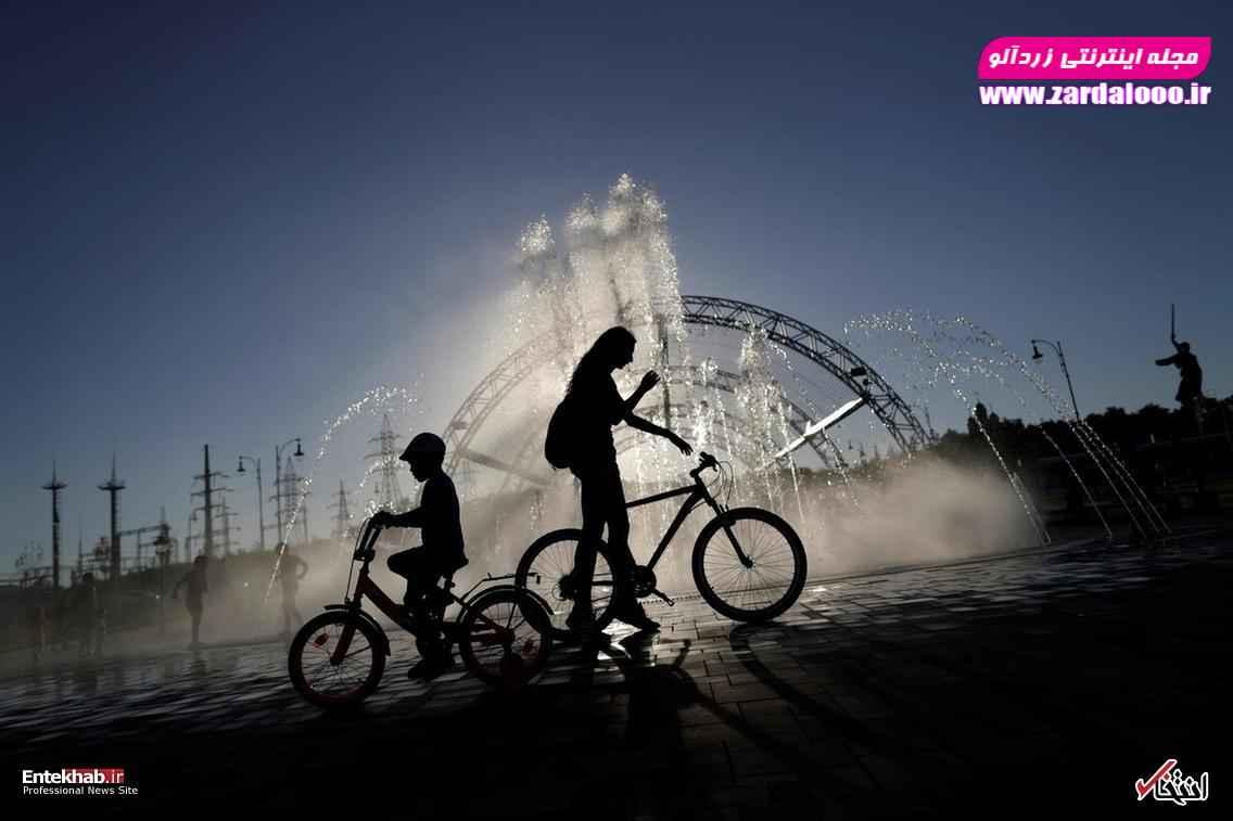 دوچرخه سواری کودکان در مقابل یک فواره در ولگاگراد روسیه