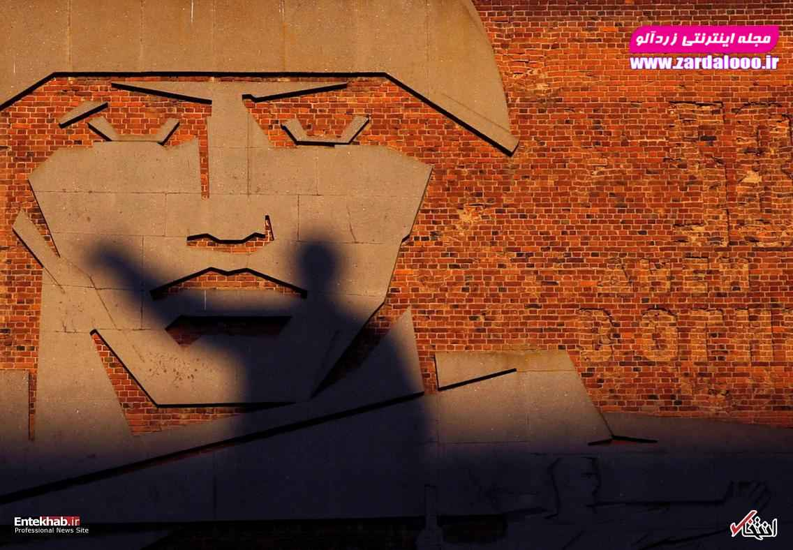 سایه مجسمه ولادیمیر لنین رهبر شوروی افتاده روی نقاشی دیواری یک سرباز
